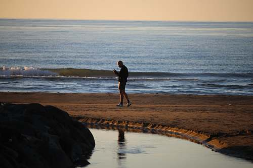 person man wearing short standing on shore nature