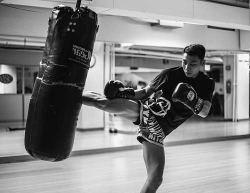 black-and-white man wearing training gloves kicking heavy bag inside gym near mirror walls boxing