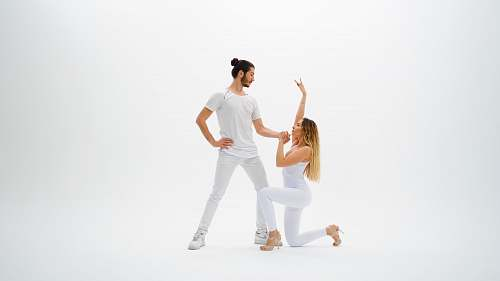 person man wearing white shirt holding hands with woman wearing white pants dance pose