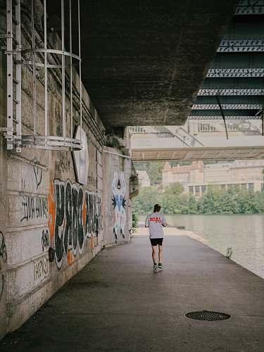 person man wearing white T-shirt walking on sidewalk sport