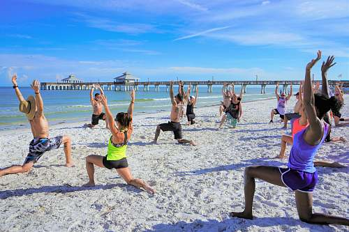 person people exercising on seashore during daytime sports