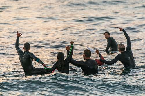 person people wearing black wetsuits in body of water people