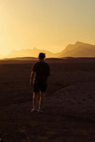 person person walking on desert during golden hour people