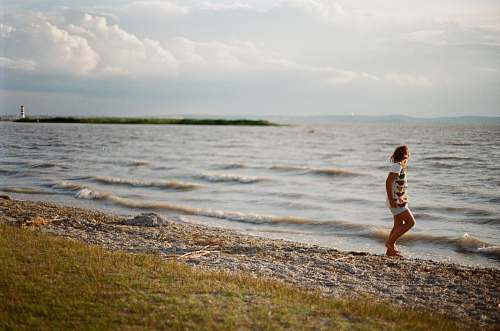 person person walking on seashore during daytime shoreline