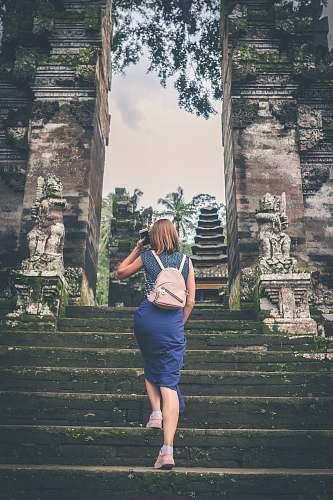 person shallow focus photography of woman in blue dress walking towards temple people