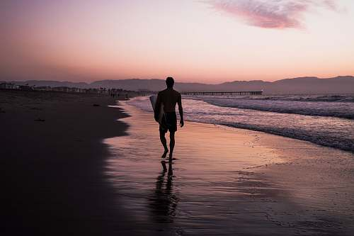 person silhouette of man walking along seashore people
