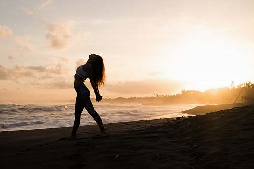 people silhouette of woman stretching her arms on seashore during sunrise person