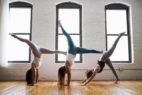 person three woman doing hand stands dance
