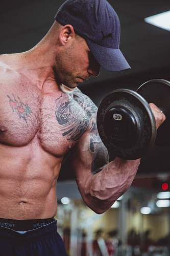 person topless man holding black dumbell on right hand people