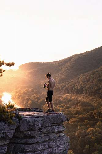 person topless man in black shorts standing near cliff at daytime people