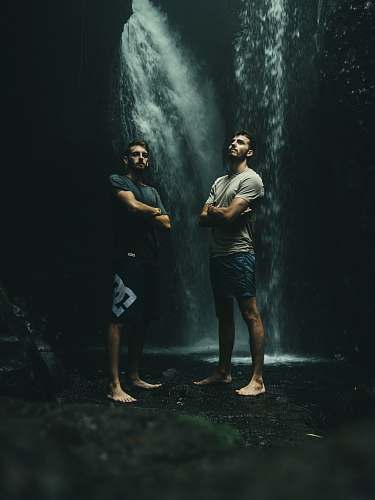 person two men standing at bottom of waterfall water