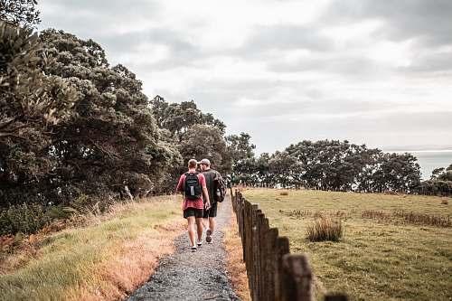 person two men walking on dirt trail beside brown fence sport