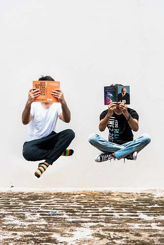 person two persons holding books shoe