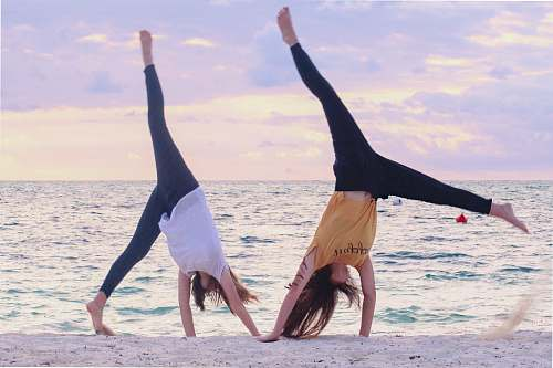 person two women on seashore during daytime working out