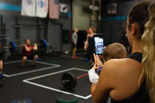 person woman carrying baby while using smartphone inside gym gym
