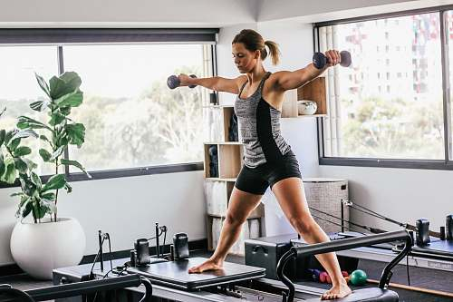 person woman doing exercise inside white room fitness