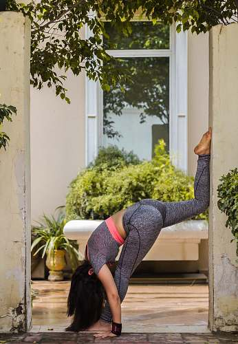 person woman doing yoga near house fitness