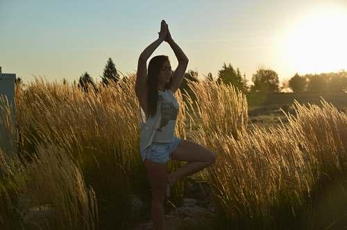 grass woman doing yoga pose outside near grass plant
