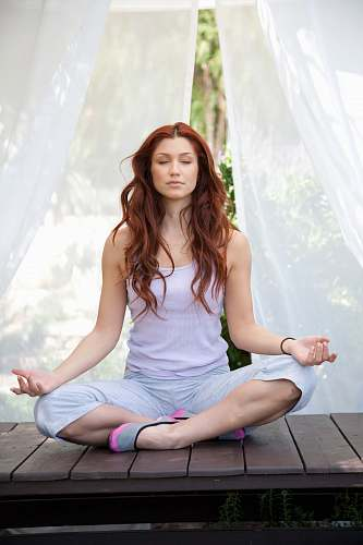 person woman doing yoga pose sitting on wooden ground working out