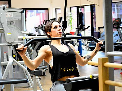 person woman exercising using lateral pull down machine at daytime fitness