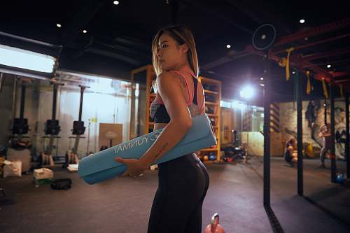 person woman holding blue exercise mat working out