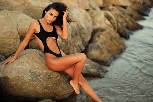 clothing woman in black swimsuit siting on rock apparel