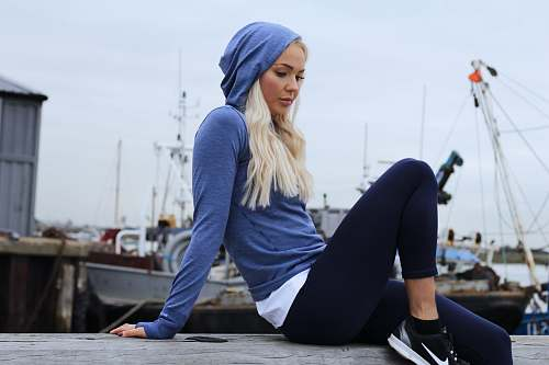 person woman in blue hoodie and black leggings lounging at gray concrete surface working out