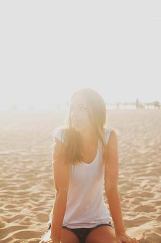 person woman in white blouse sitting on brown sand people