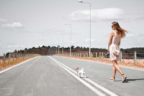 people woman in white sleeveless dress holding harness of puppy walking on asphalt road during daytime woman