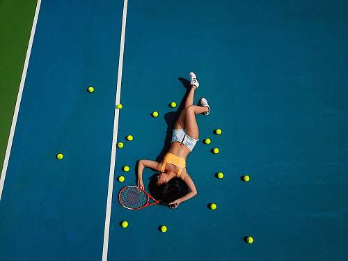 person woman in yellow crop top laying down on hard court sport