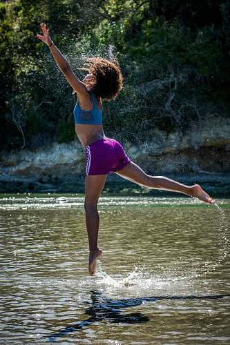 person woman jumping on body of water near trees during daytime people