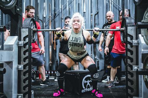 person woman lifting barbell people