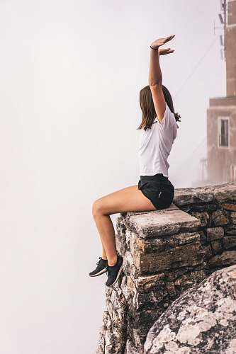 apparel woman sitting on edge while raising hand clothing
