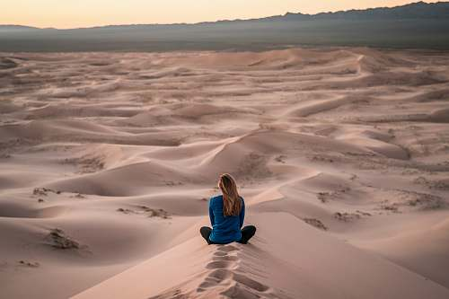 person woman sitting on sand field people