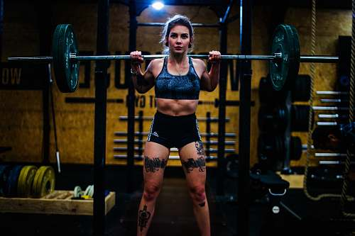 person woman standing and carrying barbell gym