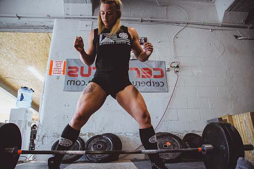 person woman standing in front of black barbell people