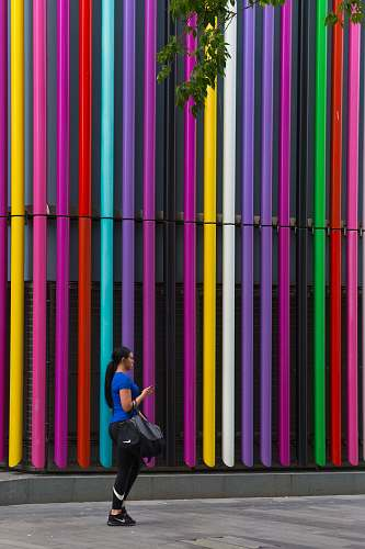 person woman standing near the multicolored building wall at daytime people