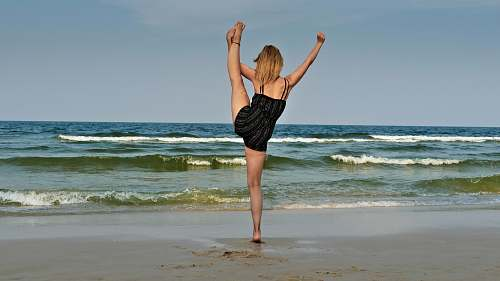 person woman standing on seashore dance pose