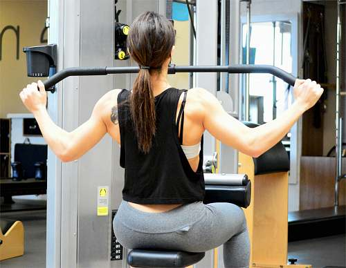 person woman wearing black sleeveless top using gym equipment people
