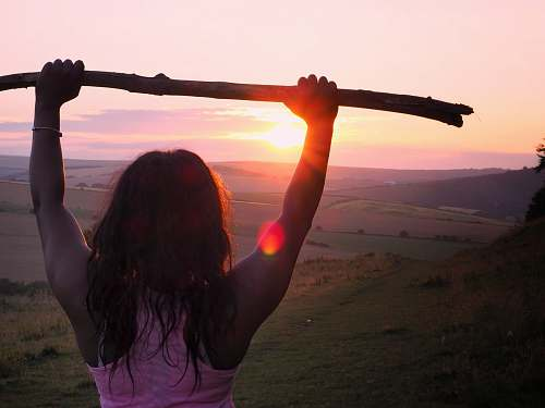 person woman wearing pink tank top holding wood stick during sunrise people