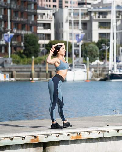 person woman wearing sports bra and yoga pants standing and bending her body during daytime water