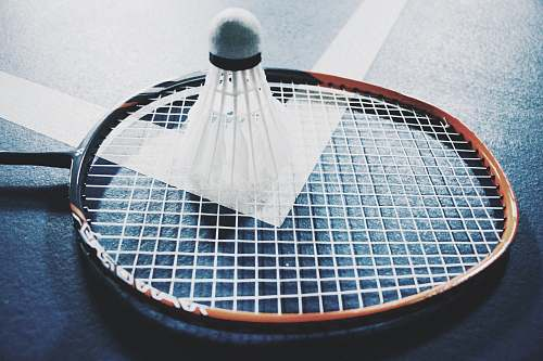 play white shuttlecock on brown and black badminton racket placed on floor game