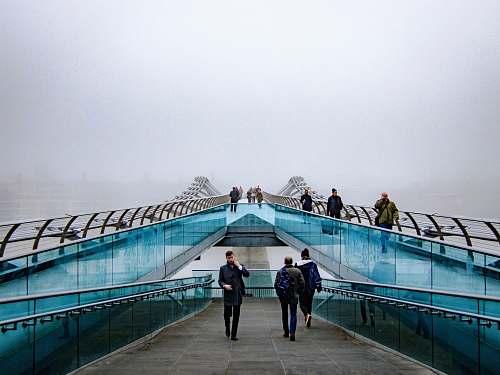 blue people walking near glass railings millennium bridge