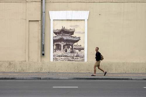 architecture minimalist photography of man walking along pagoda wall artwork building