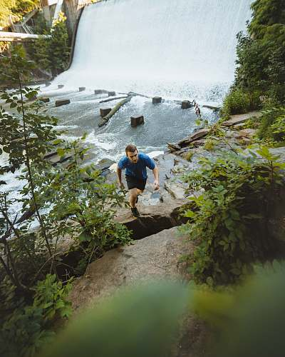 outdoors man climbing on cliff beside river river