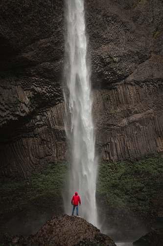 eruption man standing near waterfalls geyser