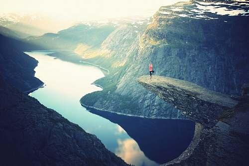 mountain person standing on rock ledge doing yoga pose yoga