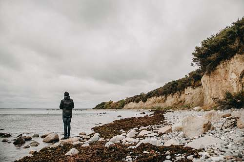 coast person standing on seashore ocean