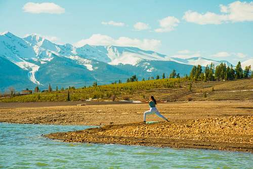 outdoors woman doing yoga near river mountain