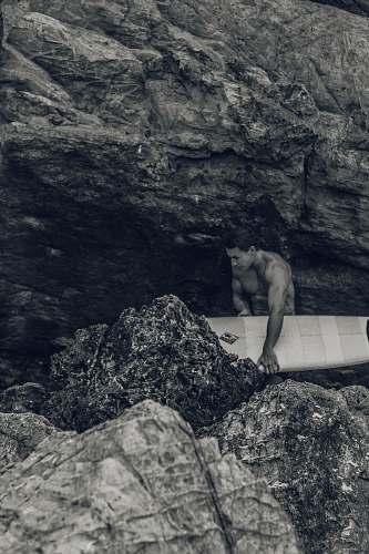 nature man holding surfboard beside rock rock